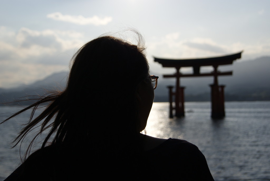 Chica mirando sobre el arco (Torii) que hay sobre el agua en el Templo de Miyajima
